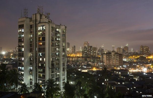 """A high-rise residential tower is seen next to shanties in Dharavi, one of Asia""""s largest slums, in Mumbai March 18, 2015. In Mumbai, the windows of new high-rise apartment blocks, old low-rise residential buildings and shantytown shacks portray the disparity in living conditions and incomes in the Indian city."""