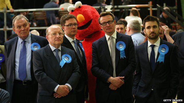 "Tory supporters with a giant ""Elmo"" behind them"