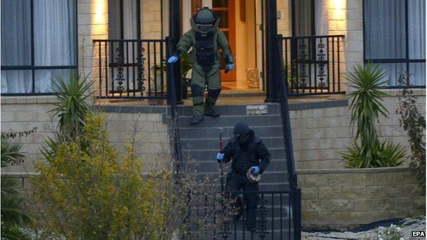 Officers wearing bombproof suits leave a house