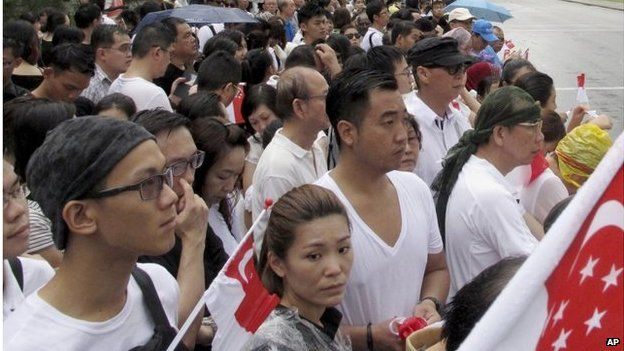 Singaporeans wait for the coffin of Lee Kuan Yew to pass during the funeral procession, Sunday, 29 March 2015, at the Padang parade grounds and City Hall in Singapore.
