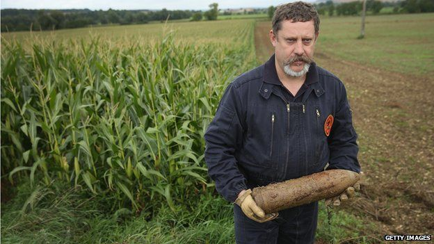 Mine-clearing specialist Raoul Weber holds an unexploded German 105mm artillery shell from World War I found by a local farmer in a corn field at Champneuville on August 26, 2014