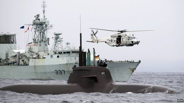 German Navy submarine U33 (front), Canadian Navy's HMCS Fredericton (left) and a Dutch helicopter (right) participate in NATO's Dynamic Mongoose anti-submarine exercise in the North Sea