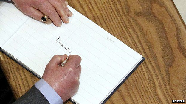 Prince Charles signs a visitor's book in Belfast