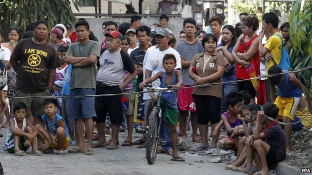Filipino relatives of missing factory workers wait for updates following a fire at a footwear factory in Valenzuela city, east of Manila, Philippines, 14 May 2015.