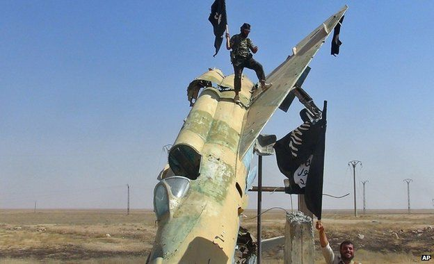 Islamic State fighters wave the group's flag near a Syrian fighter jet in Raqqa in Syria, undated