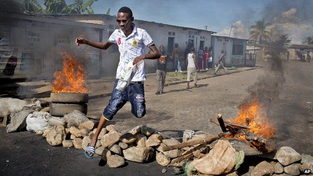 A civilian jumps over a burning barricade of rocks erected by residents to protect themselves from police, in a northern district of the capital Bujumbura, in Burundi 14 May 2015