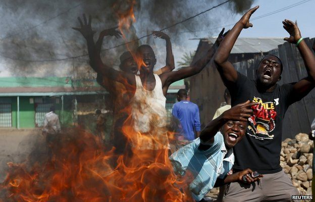 "Protesters, who are against President Pierre Nkurunziza""s decision to run for a third term, gesture in front of a burning barricade in Bujumbura, Burundi 14 May 2015."