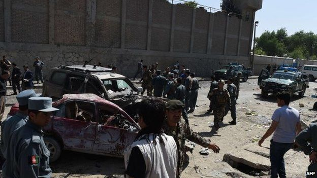 Afghan and foreign security forces inspect the site of a suicide attack in Kabul, 17 May 2015