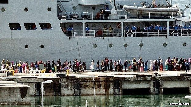 Rohingya women migrants and children stand in a queue to board a Malaysian Navy ship at the naval base in Langkawi on May 14, 2015 to be transferred to a mainland immigration depot.