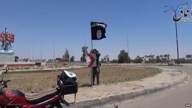 A screen grab from IS video uploaded on 18 May 2015 shows an IS fighter hanging the group's flag in a street of Ramadi, the Iraqi capital of Anbar province, a day after the city was captured by IS.