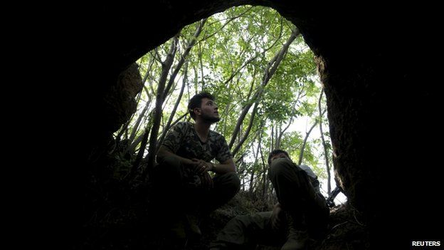 Rebel fighters of the Al-Furqan brigade sit at the entrance of a cave May 17, 2015