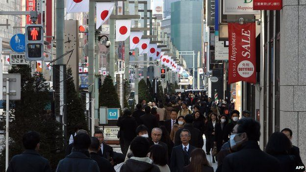 Shoppers walk down a busy street in the Ginza shopping district in central Tokyo