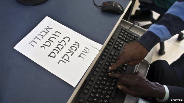 A Hebrew teacher (right), an Israeli of Ethiopian descent, shows a new immigrant from Ethiopia letters on a keyboard at an absorption centre for new immigrants near Jerusalem