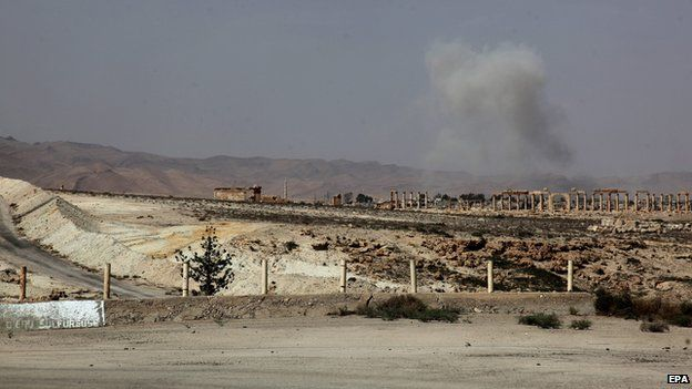 Smoke rises after a Syrian Rocket launcher shell on enemy positions in the ancient oasis city of Palmyra on 19 May