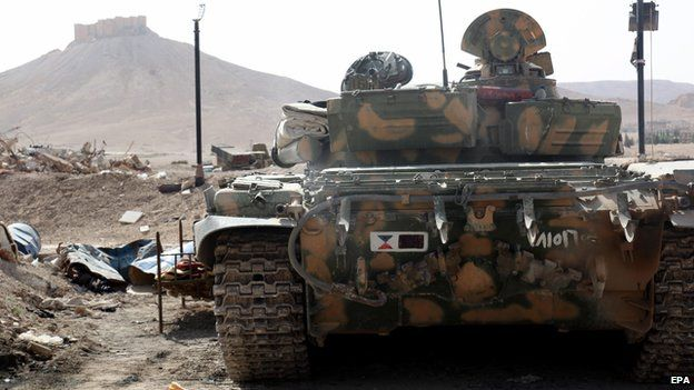 A Syrian armoured tank takes up position during fighting against IS militants in the ancient oasis city of Palmyra