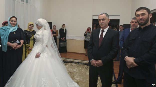 Kheda Goylabiyeva and Chechen police officer Nazhud Guchigov, second right, stand in a wedding registry office in Chechnya's provincial capital Grozny, 16 May 2015.