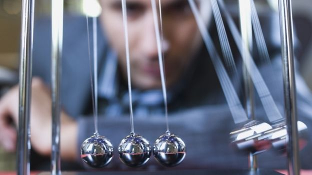 Businessman looks at Newton's cradle