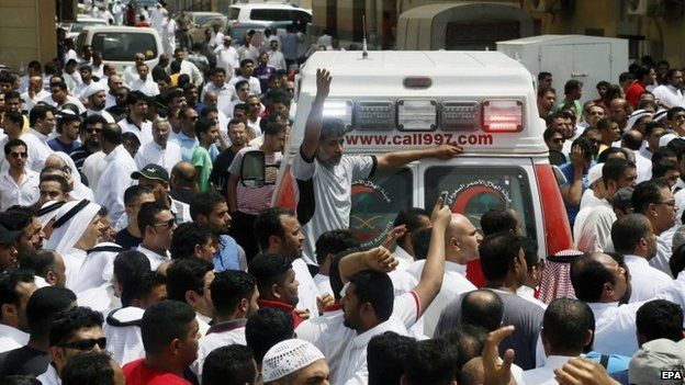 People gather around an ambulance following a suicide attack on the Shia Imam Ali mosque, in a village in Qatif, Saudi Arabia's Eastern Province, on Friday