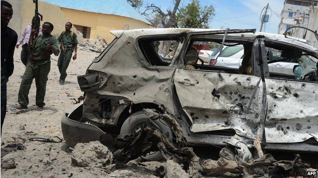Somali government soldiers walk around a destroyed car at the site of car bomb blast in front of the Makka Al Mukarrama Hotel in Mogadishu, on March 15, 2014.
