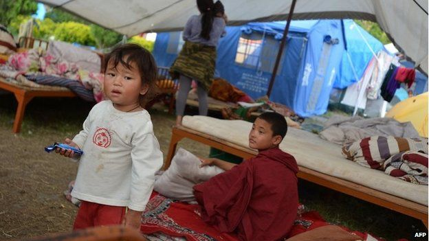 Children sit inside a makeshift tent for earthquake victims in Kathmandu