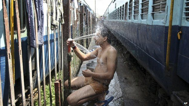 Train passenger cools off at railway station in Jammu. 25 May 2015
