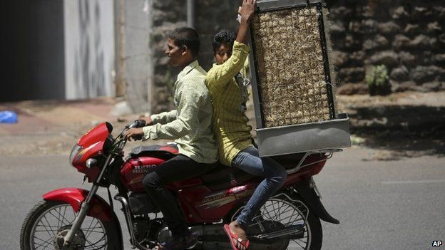 An Indian man carries a cooler on a motorcycle during hot summer day in Hyderabad, India, Thursday, May 21, 2015.