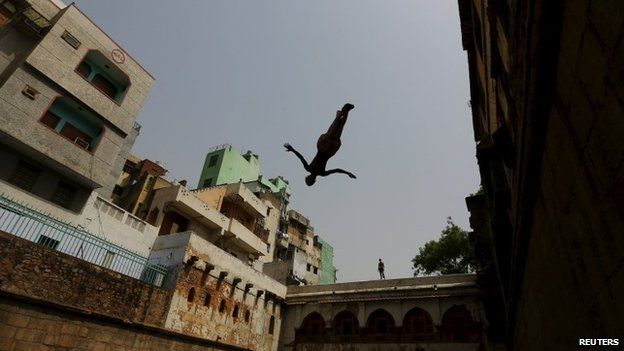 A boy jumps into a step well built inside the shrine of Sufi Saint Nizamuddin Auliya in New Delhi, India May 24, 2015.