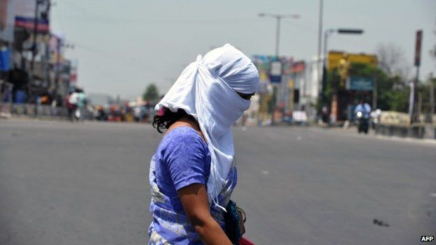 An Indian woman with her face covered crosses the road on the outskirts of Hyderabad on May 25, 2015