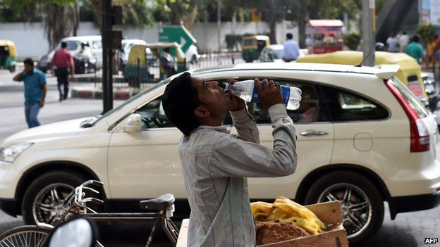 An Indian labourer takes a break as he drinks water to get respite from heat in New Delhi on May 26, 2015
