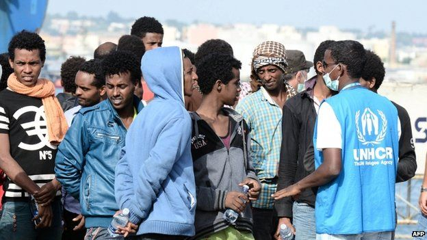 A UN refugee agency worker speaks to migrants disembarking in the port of Augusta (21 May 2015)