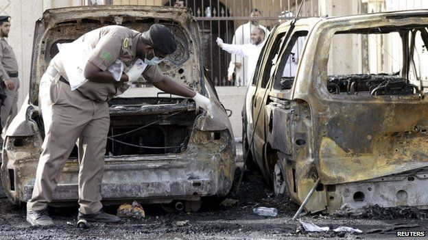 A policeman inspects a car damaged by a suicide blast at a mosque in eastern Saudi Arabia