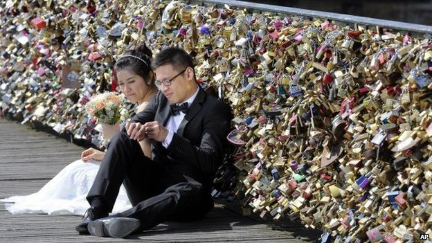 This Wednesday April 16, 2014 file photo shows a newly wed couple resting on the Pont des Arts in Paris, France