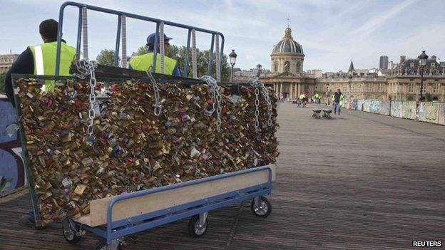 "City municipal employees remove iron grills covered with ""lovelocks"" on the Pont des Arts which crosses over the River Seine in Paris, France, June 1, 2015"
