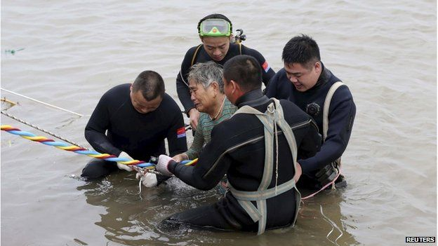 A woman is helped after being pulled out by divers from a sunken ship in Jianli, Hubei province, China, 2 June 2015.