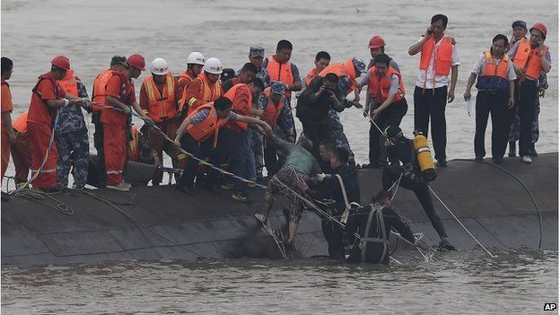 In this photo released by China's Xinhua News Agency, rescuers save a survivor, center, from the overturned passenger ship in the Jianli section of the Yangtze River in central China's Hubei Province Tuesday, 2 June 2015