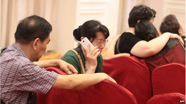 "A relative (C) of passengers on board the Dongfangzhixing or ""Eastern Star"" which sank en route from the eastern city of Nanjing to the southwestern city of Chongqing, cries while talking on a mobile phone at a hotel in Nanjing, east China's Jiangsu province on 2 June 2015"