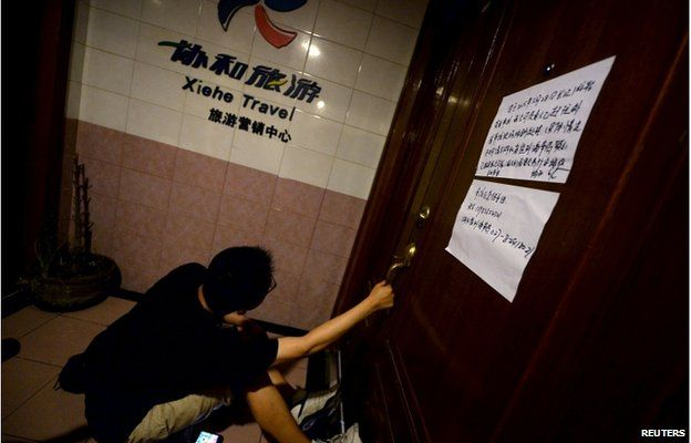 A relative of passengers on the ship which sank at the Jianli section of Yangtze River, in Hubei province, pulls the door of a closed office of Xiehe Travel in Shanghai, China, 2 June 2015.
