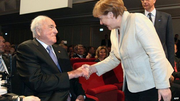 German chancellor Angela Merkel (R) shakes hands with former chancellor Helmut Kohl (L) sitting on his wheelchair in Ludwigshafen am Rhein, western Germany, on 23 April 2015