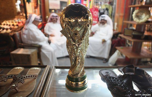 Arab men sit at a shoemaker's stall with a replica of the FIFA World Cup trophy in the Souq Waqif traditional market 24 October 2011