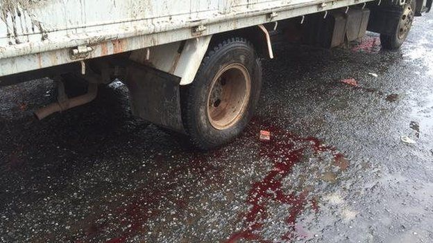 Blood on the road under a truck