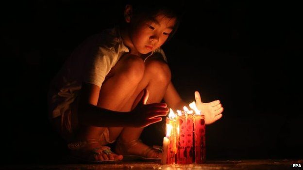 A girl lights candles to pray for victims of a capsized tourist ship in Jianli, Hubei province, China, 05 June 2015.