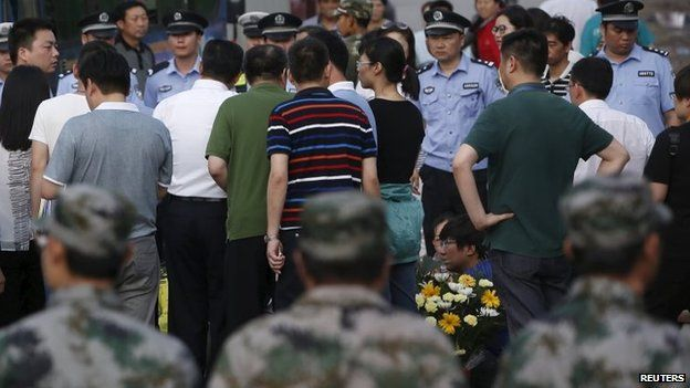 A relative of a missing passenger aboard the capsized ship Eastern Star holds flowers as he is surrounded by paramilitary soldiers after breaking through the first police cordon in the direction of the site near a funeral parlor in Jianli, Hubei province, China, June 5, 2015.