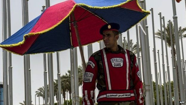 An Egyptian Republican Guard stands guard under an umbrella outside the venue of a ministerial meeting of the Common Market for Eastern and Southern Africa, East African Community and Southern African Development Community, in the Egyptian Red Sea resort of Sharm al-Sheikh, on 9 June 2015, on the eve of a summit to launch a three-way free trade area.