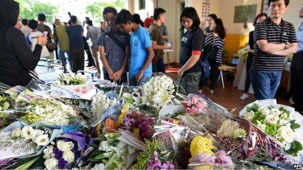 "People look at bouquets of flowers in memory of the victims from an earthquake on Malaysia""s Mount Kinabalu, placed on a table at the Tanjong Katong Primary School in Singapore on 7 June 2015"
