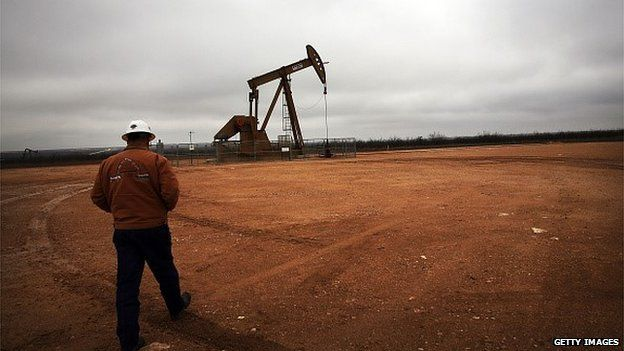 A member of staff approaching a nodding donkey extracting oil in Texas.