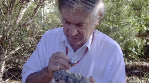 Dr Andrew Glikson examines a sample of suevite - a rock with partially melted material formed during an impact.