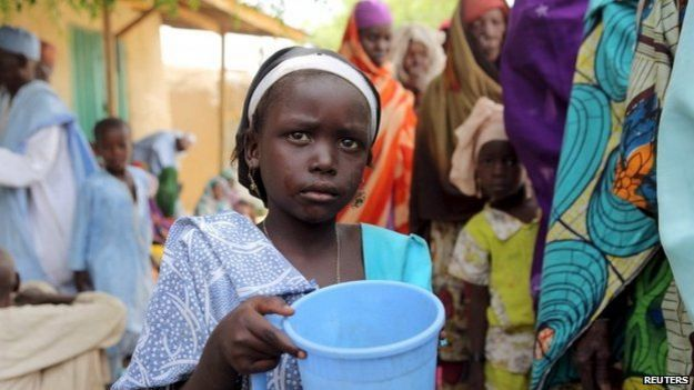 A girl drinks water as women queue for blankets and food given out by Nigerien soldiers in Damasak on 24 March 2015