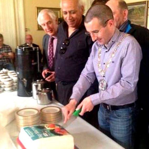 Andrew Muir cutting a substitute cake