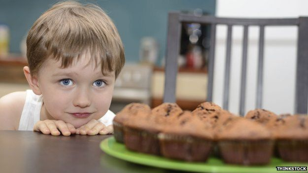 Child eyeing up cake