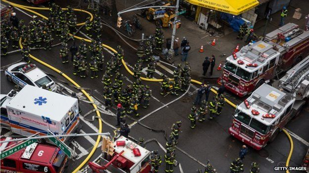 New York City Fire Department staff work to extinguish a fire as a building burns after an explosion
